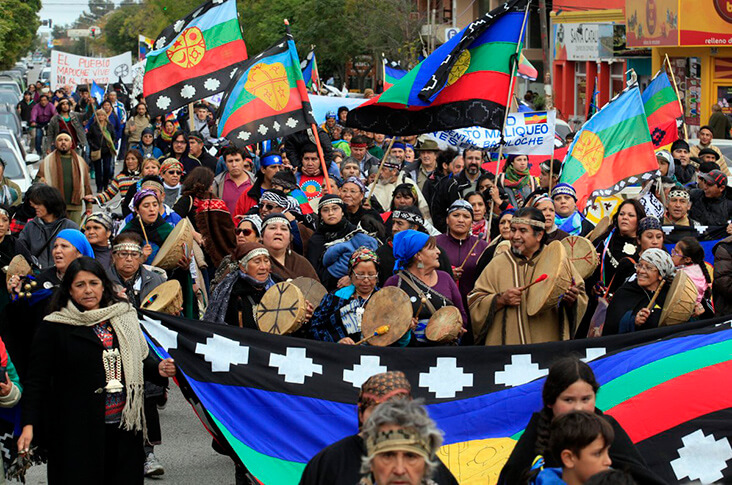 The Mapuche people marching with colored flags